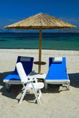 Beach chairs with straw umbrellas — Stock Photo