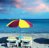 Colourful beach chairs with straw umbrellas on a beautiful sandy — Stock Photo