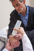 Doctor preparing arm for sonography — Stock Photo