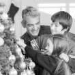 Father with son and daughter decorating Christmas tree. Family C — Stock Photo #50995521