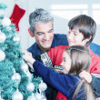Father with son and daughter decorating Christmas tree. Family C — Stock Photo #50995605