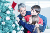 Father with son and daughter decorating Christmas tree. Family C — Stock Photo