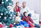 Family near Chrismas tree awaiting Santa Claus arrival — Stock Photo