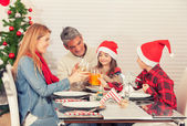 Family Christmas table with tree on background. Parents and chil — Stock Photo