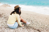 Beautiful young woman sitting on a beach and looking at sea — Stock Photo