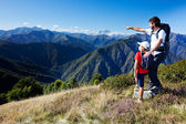 Man and young boy standing in a mountain meadow — Stock Photo