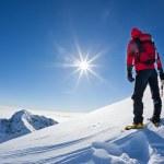 Mountaineer når toppen av en snöig berg i en solig winte — Stockfoto