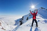 Alpinista llega a la cima de una montaña nevada en un soleado winte — Foto de Stock
