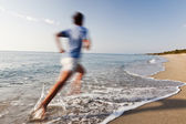Young man running on a beach. — Stock Photo