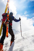 Ski mountaineer walking up along a steep snowy ridge with the s — Stock Photo