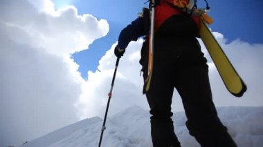 Ski mountaineer walking up along a steep snowy ridge with the skis in the backpack. — Stock Video