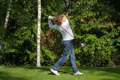 Young golf player with driver teeing-off — Stock Photo