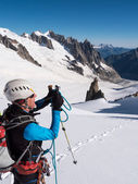 Mountaineer taking picture with a camera in the mountains. — Stock Photo