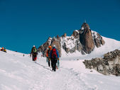 The Aiguille du Midi peak, in foreground a group of mountaineers — Stok fotoğraf