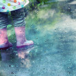 Stock Photo: Cute little girl is playing in muddy puddles