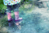 Cute little girl is playing in muddy puddles — Stok fotoğraf
