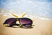 Seastar and sunglasses on a beach — Stok fotoğraf