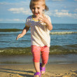 Little girl child running on the seaside under blue sky — Stock Photo