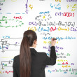 Businesswoman drawing formula — Stock Photo #12219152