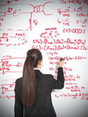 Businesswoman drawing formula — Stok fotoğraf