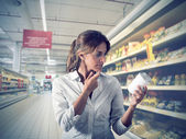 Girl unsure at supermarket — Stok fotoğraf