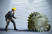 Businessman turning a gear system — Stock Photo