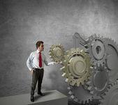 Uomo d'affari trasformando un sistema di ingranaggi — Foto Stock