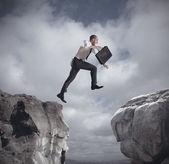 Affärsman hoppa över bergen — Stockfoto