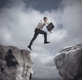 Businessman jumping over the mountains — Stock Photo