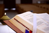 Bible and candle in a church — Stock Photo