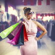 Beautiful young woman holding shopping bags — Stock Photo