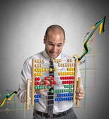 Businessman with abacus calculates — Stock Photo