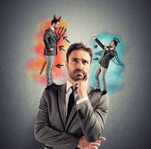 Businessman with angel and devil — Stock Photo