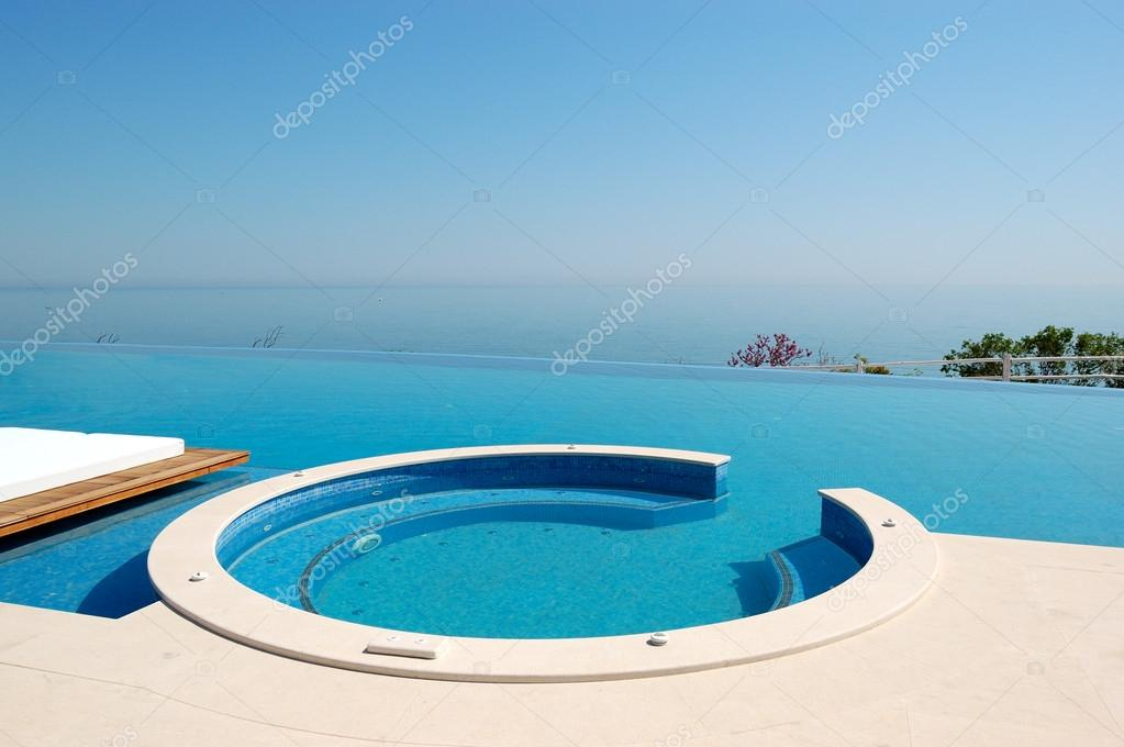 infinity swimming pool with jacuzzi by beach at the modern luxur stock photo slava296 18228387. Black Bedroom Furniture Sets. Home Design Ideas
