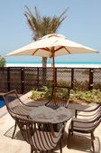 Chairs and umbrella near swimming pool by a beach of the luxury — Stock Photo
