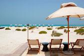 Sunbeds and umbrellas at the Beach of luxury hotel, Abu Dhabi, U — Stock Photo