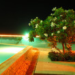 Swimming pool and beach of the luxury hotel in night illuminatio — Stock Photo