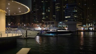 The night illumination of Dubai Marina and luxury yachts. It is an artificial canal city, built along a two mile (3 km) stretch of Persian Gulf shoreline. Dubai, UAE — Stock Video