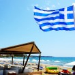 PATRONIKOLEIKA, GREECE - JUNE 10: The Greek Flag on the beach an — Stock Photo