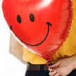 Young man holding a red heart shaped balloon - Stock Photo