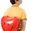 Royalty-Free Stock Photo: Young man holding a red heart shaped balloon