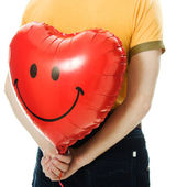 Young man holding a red heart shaped balloon — Stock Photo