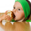Pretty little girl eats bread - Stock Photo