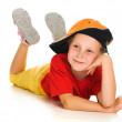 Royalty-Free Stock Photo: A cheerful little child with funny cap is lying