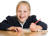 Schoolgirl writes at a table — Stock Photo