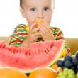 Baby eats fruit on a white background - Stock Photo