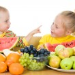 Royalty-Free Stock Photo: Two children eat fruit at a table