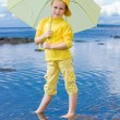 Girl with umbrella on a beach — Stock Photo