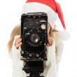 Girl in a Christmas costume with old camera — Stock Photo #13674164