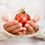 Woman's hand holding a Christmas ball — Stock Photo #13683608